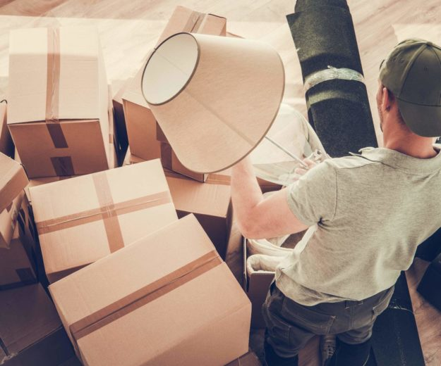 Man Moving Out From His Home. Staying Between Cardboard Boxes Preparing to Pack His Lamp.