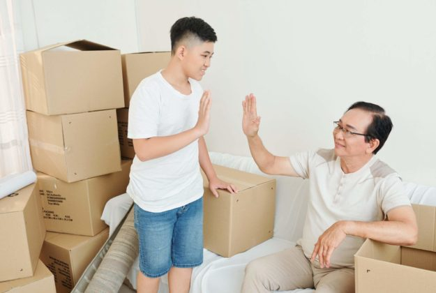 Teenage boy giving his grandfather high five after packing all belongings in cardboard boxes