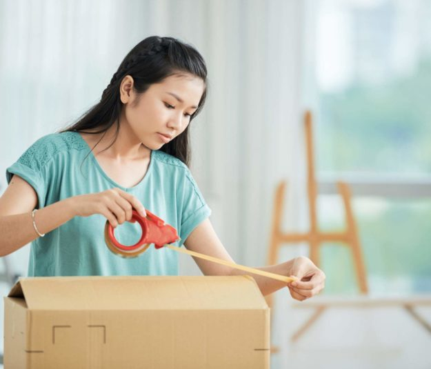 Asian young woman packing the cardboard box with adhesive tape she moving the new house